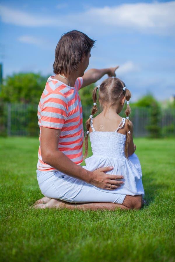 Achtermening van vader met zijn dochter binnen zitting royalty-vrije stock afbeelding