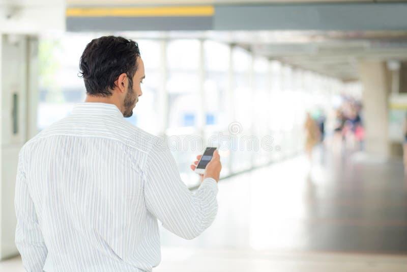 Achtermening van a van zakenman die mobiele smartphone gebruiken stock afbeelding