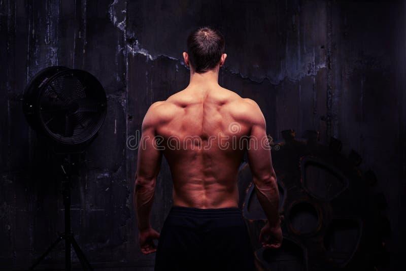 Achtermening van volkomen opgeleid mannelijk lichaam tegen donkere ruwe muur stock afbeelding