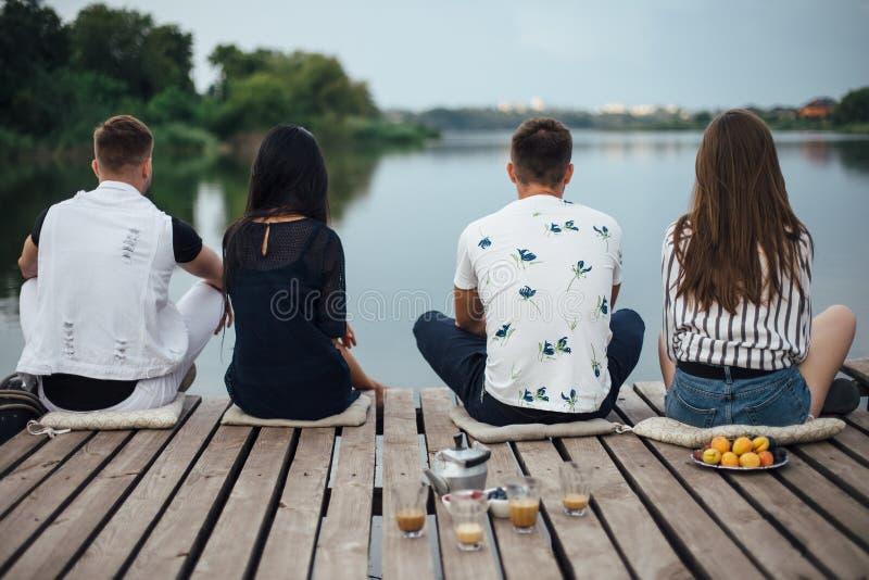 Achtermening van vrienden die op rivierpijler ontspannen royalty-vrije stock afbeeldingen