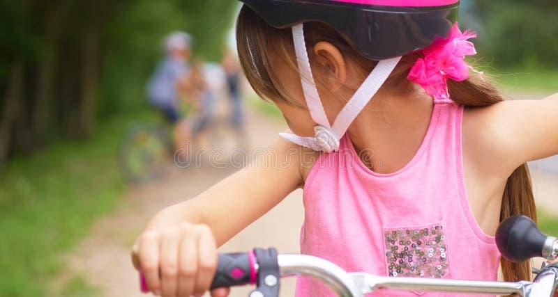 Achtermening van vrolijk meisje in een roze beschermende helm die bij haar vrienden loking en een fiets berijden royalty-vrije stock foto