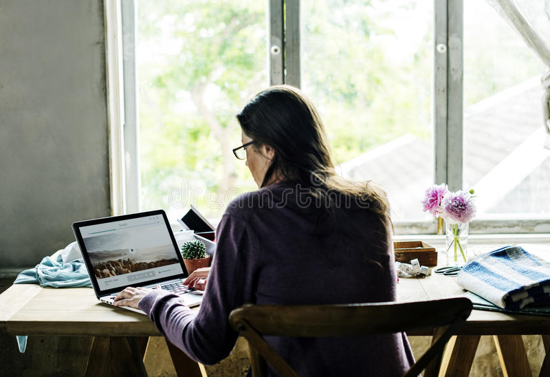 Achtermening van vrouw die aan computerlaptop werken op houten lijst stock afbeelding