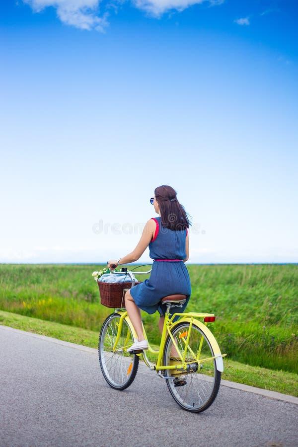 Achtermening van vrouw die retro fiets in platteland berijden stock foto