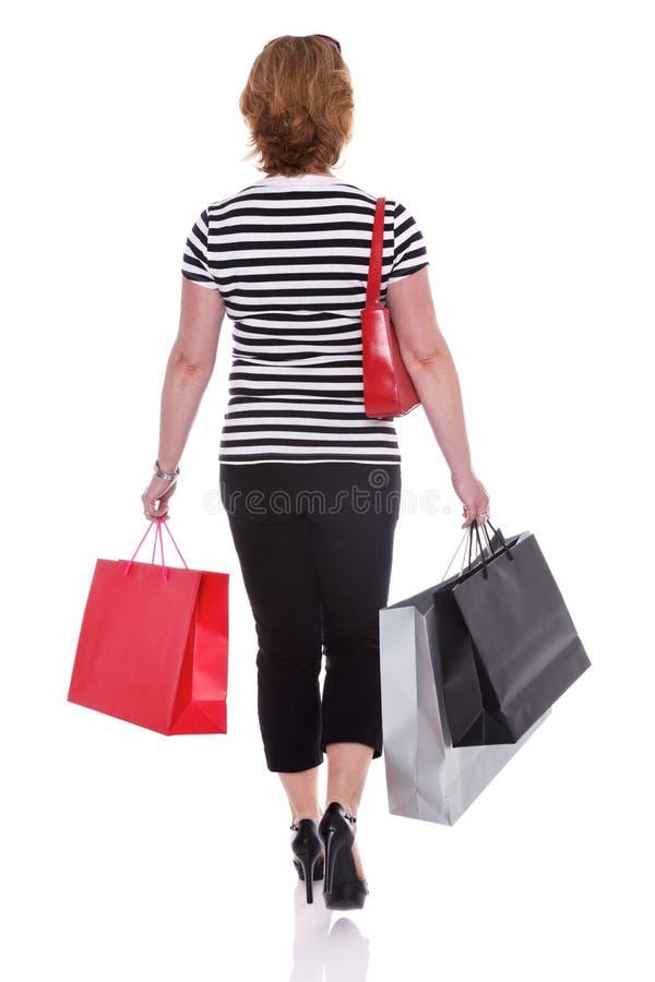 Achtermening van vrouw dragende het winkelen geïsoleerde zakken. stock foto's