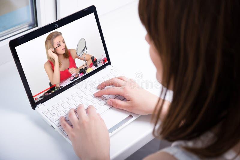 Achtermening van vrouw het letten op de video van de schoonheidsblog op laptop thuis stock afbeeldingen