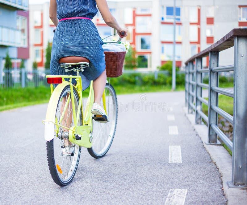 Achtermening van vrouw in kleding die uitstekende fiets met mand berijden stock afbeeldingen