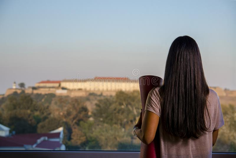 Achtermening van vrouw met de lettende op stad van de yogamat door het venster stock foto's