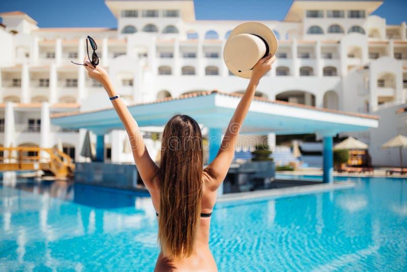 Achtermening van vrouw met handen omhoog met hoed en zonnebril die van haar vakantie in zwembad genieten royalty-vrije stock foto's