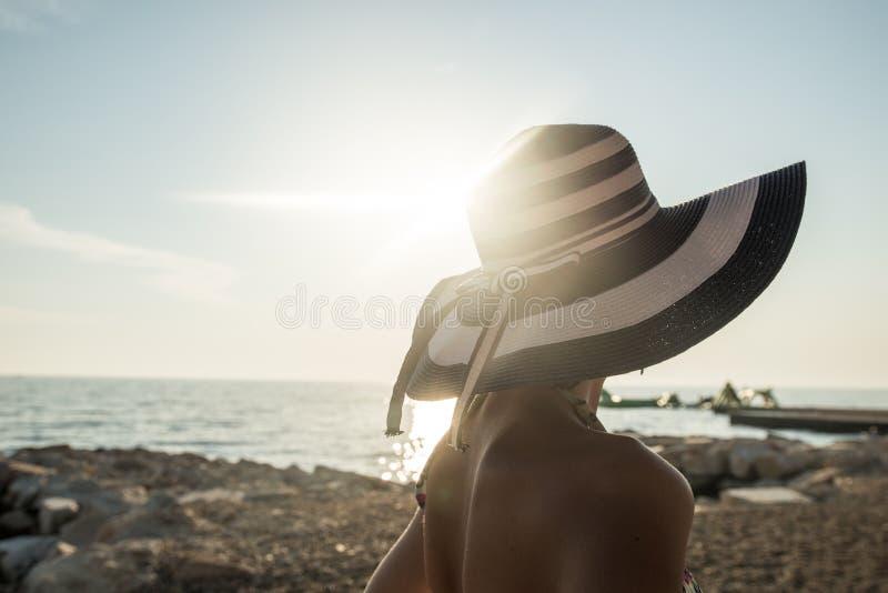 Achtermening van vrouw in zwempak bij de strand het letten op zonsondergang over stock fotografie