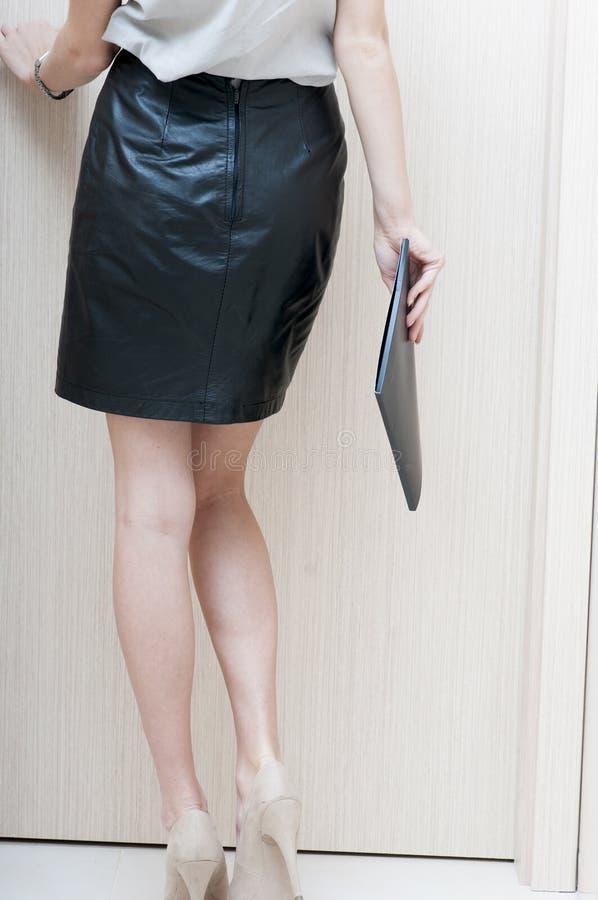 Achtermening van vrouwelijke lange die benen in beige schoenen worden geschoeid stock foto's