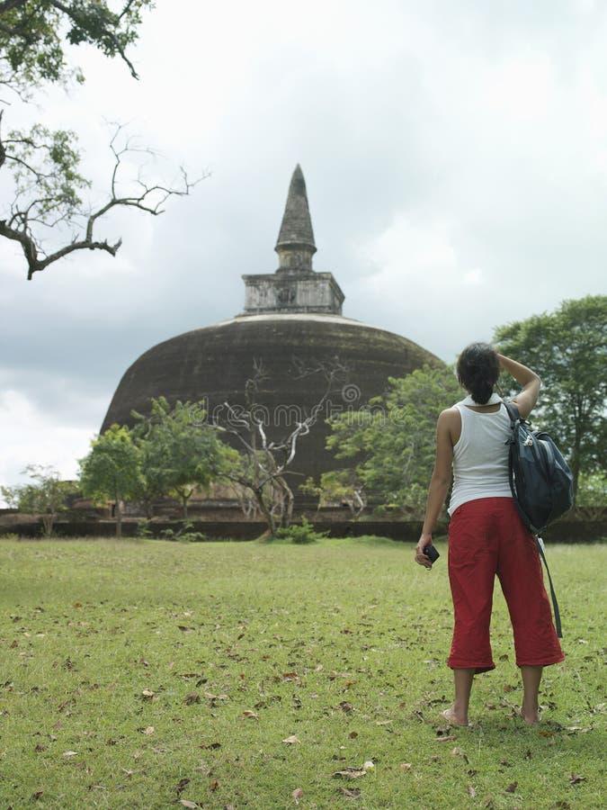 Achtermening van Vrouwelijke Toerist die in Stupa bekijken stock foto