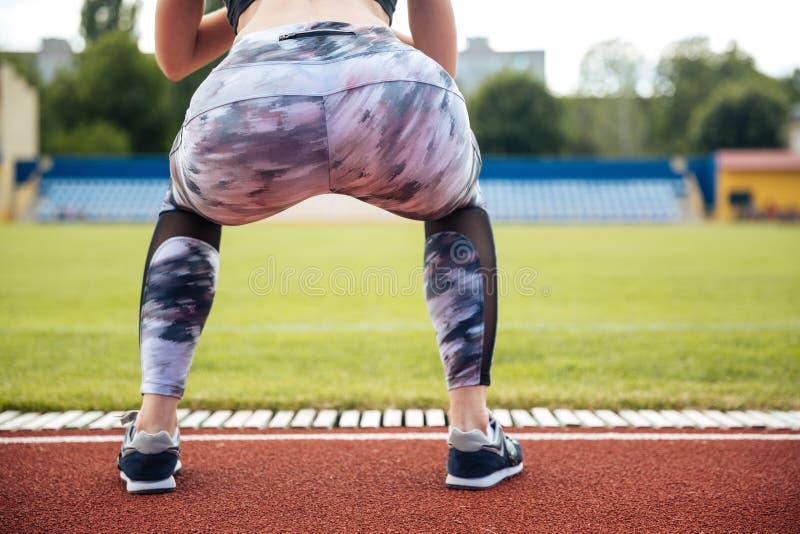 Achtermening van vrouwenatleet in beenkappen die hurkzit doen stock afbeeldingen