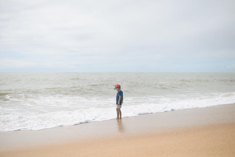 Achtermening van weinig jongen die langs het strand tijdens de zonsondergang lopen royalty-vrije stock afbeeldingen