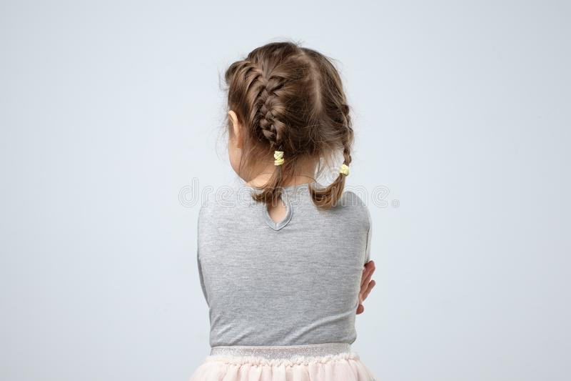 Achtermening van weinig Kaukasisch meisje Het jonge geitje wordt verloren of wordt beledigd op ouders stock afbeeldingen