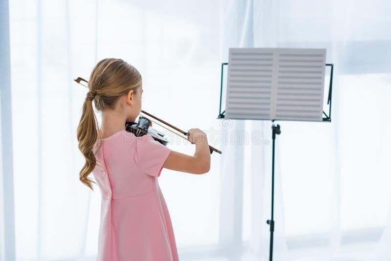 achtermening van weinig kind in roze kleding het spelen viool stock foto