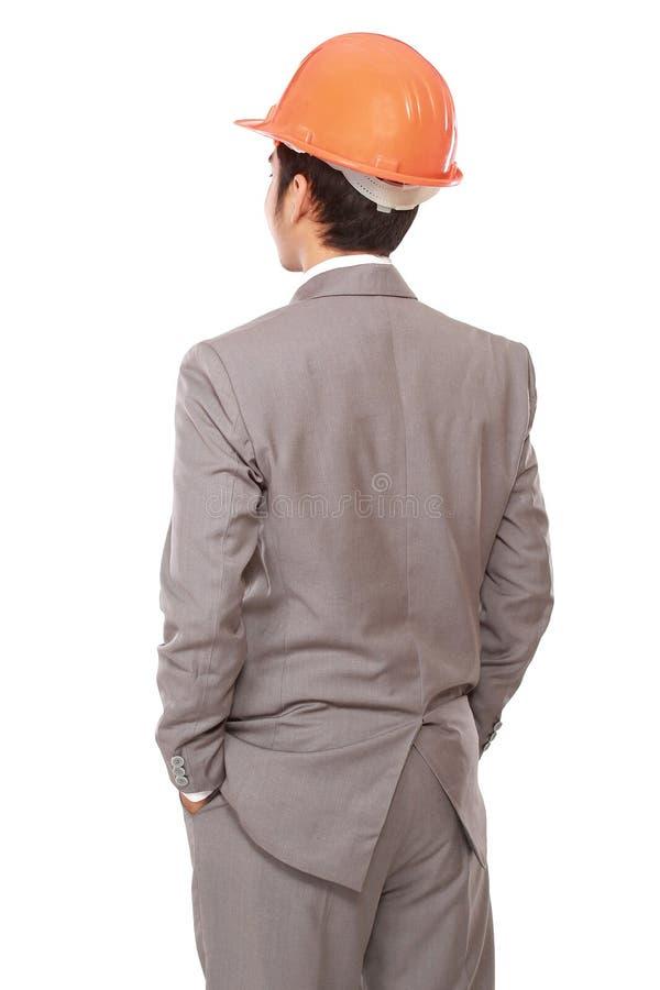 Achtermening van zakenman in de helm van de oranje bouwer royalty-vrije stock afbeeldingen