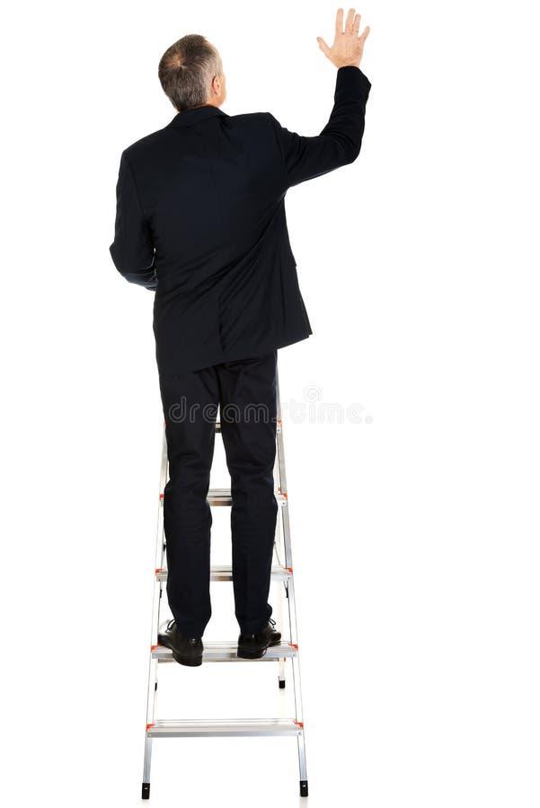 Achtermening van zakenman die ladder beklimmen royalty-vrije stock afbeeldingen