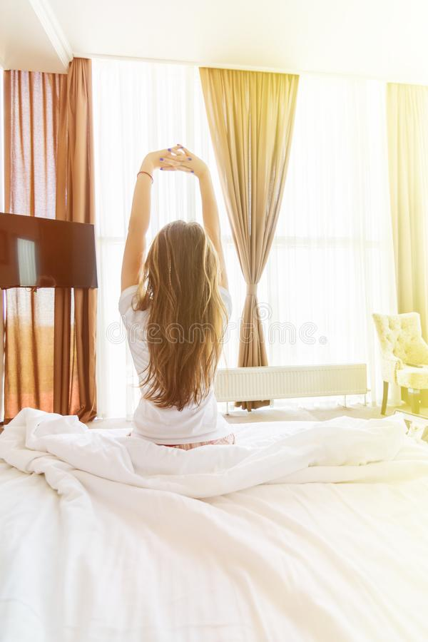 Achtermening van zich het jonge vrouw uitrekken in bed na kielzog omhoog in ochtend met zonlicht stock foto's