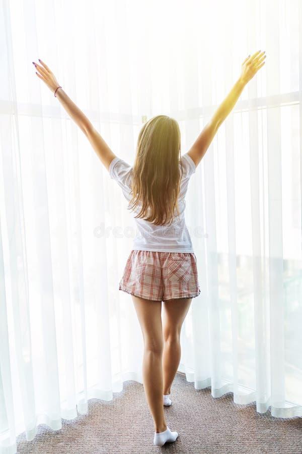 Achtermening van zich het jonge vrouw uitrekken in bed na kielzog omhoog in ochtend met zonlicht royalty-vrije stock fotografie