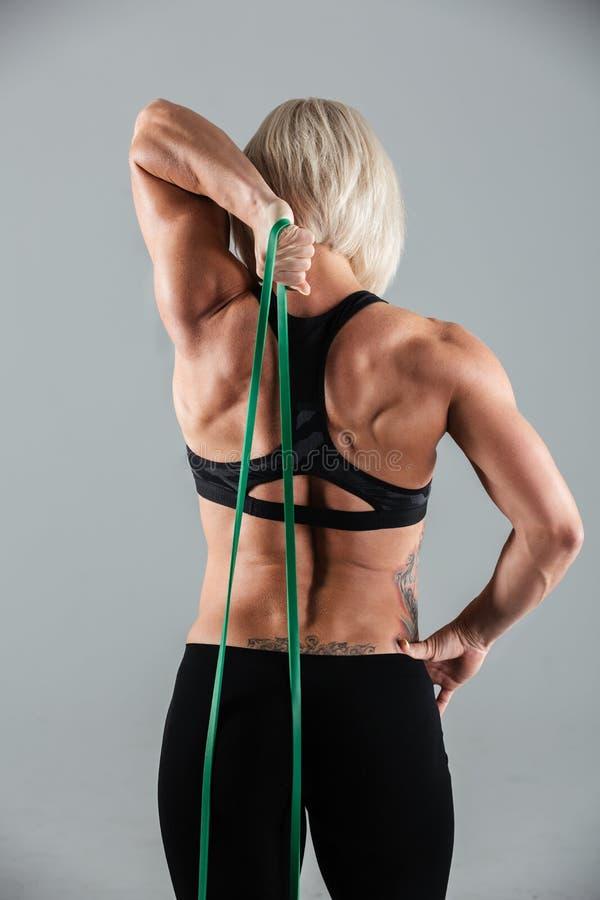 Achtermening van zich het spiergeschiktheidsmeisje uitrekken met elastische rubbe stock afbeeldingen