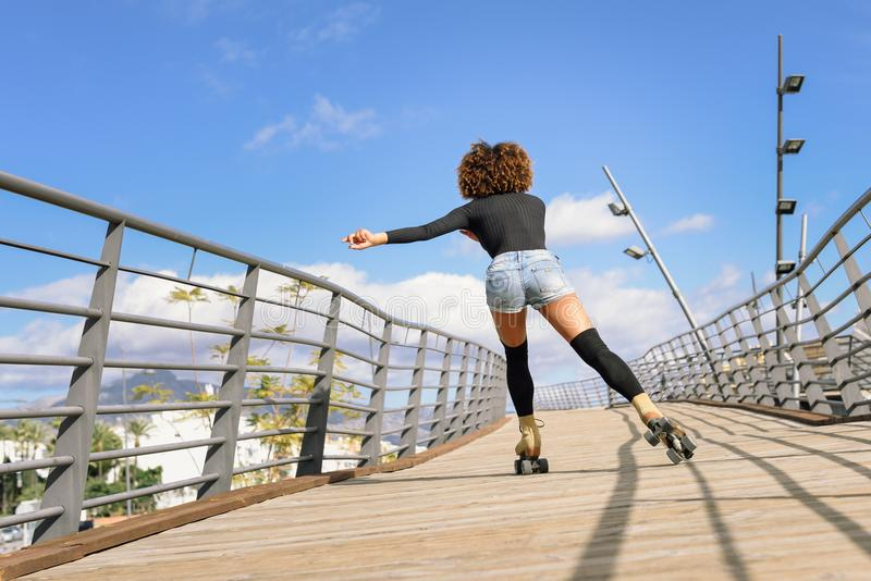Achtermening van zwarte op rolschaatsen die op stedelijke brug berijden royalty-vrije stock afbeelding