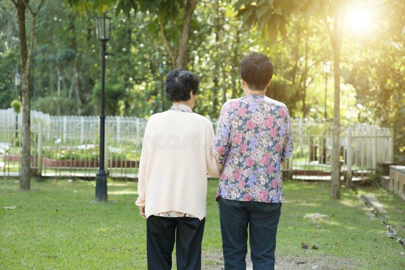 Achtermenings Aziatische bejaarden die in tuinpark lopen stock foto's