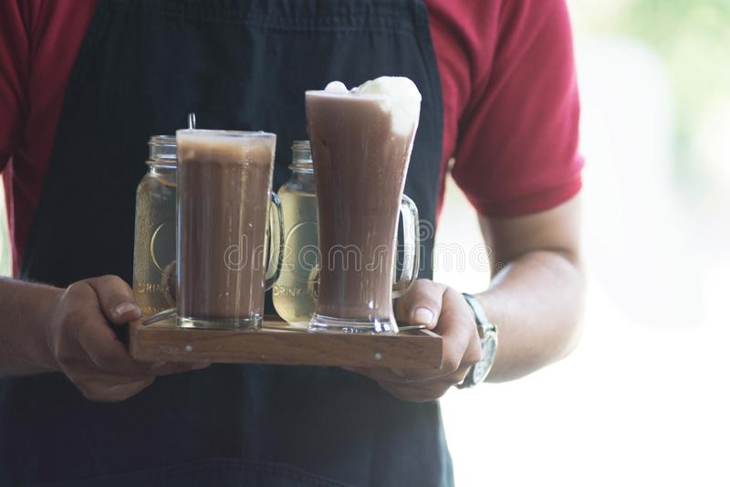 Achtermenings dichte omhooggaande mannelijke kelners die drank dienen bij koffie in daglicht stock fotografie