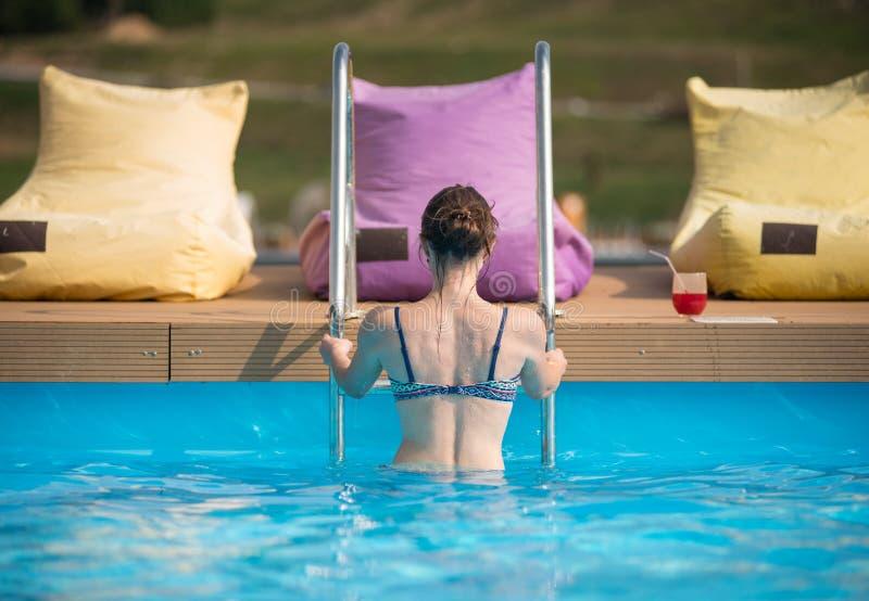 Achtermenings jong wijfje in zwempak die uit uit het water van een zwembad bij de toevlucht komen royalty-vrije stock afbeelding