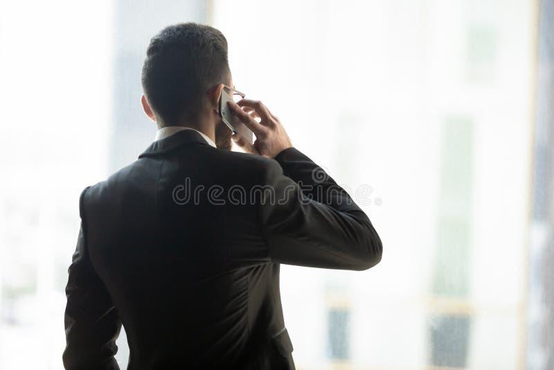 Achtermenings zekere zakenman die op telefoon met partner spreken royalty-vrije stock foto