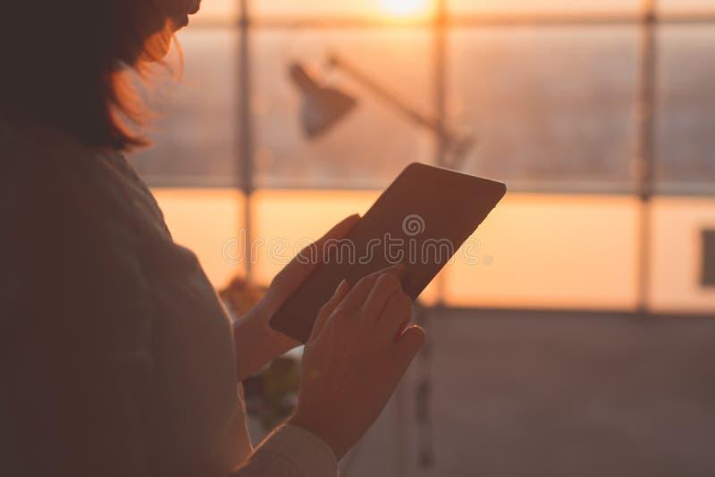 Achtermeningsbeeld die van vrouwelijke handen tabletpc houden, typend, gebruikend touchscreen en WiFi Internet op modern huiskant royalty-vrije stock fotografie