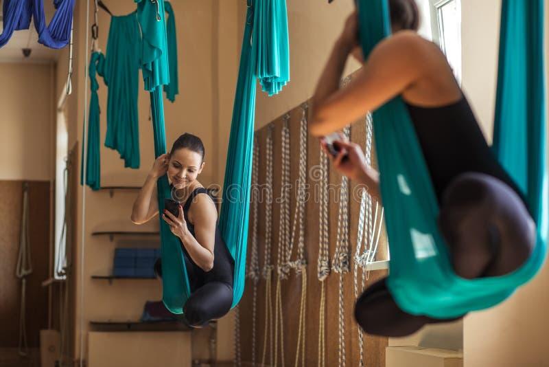 Achtermeningsfoto van een aantrekkelijke sportvrouw die op de hangmat met telefoon hangen stock fotografie