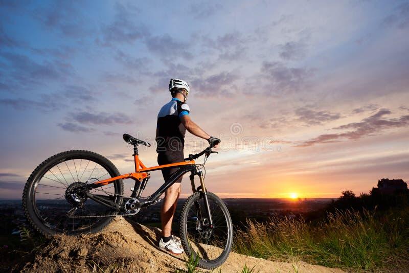 Achtermeningskerel met bergfiets die zich op heuvel op de achtergrond van zonsondergang bevinden stock afbeelding