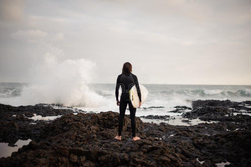 Achtermeningsmens die zich met een witte branding in zijn handen op het strand bevinden royalty-vrije stock fotografie