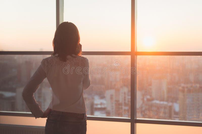 Achtermeningsportret die van jonge werknemer het spreken gebruikend celtelefoon, uit het venster kijken Wijfje die bedrijfs bezig stock afbeeldingen