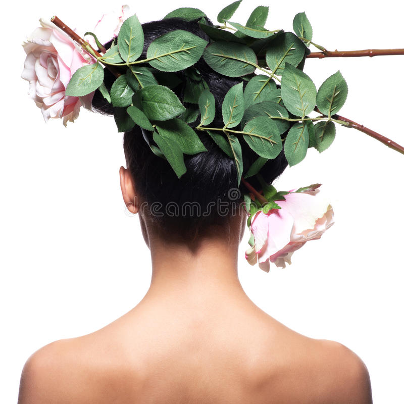 Achtermeningsportret van de vrouw met roze bloemen in haar stock foto's