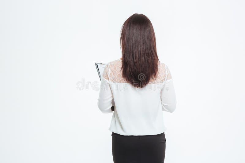 Achtermeningsportret van een onderneemster die zich met klembord bevinden royalty-vrije stock foto