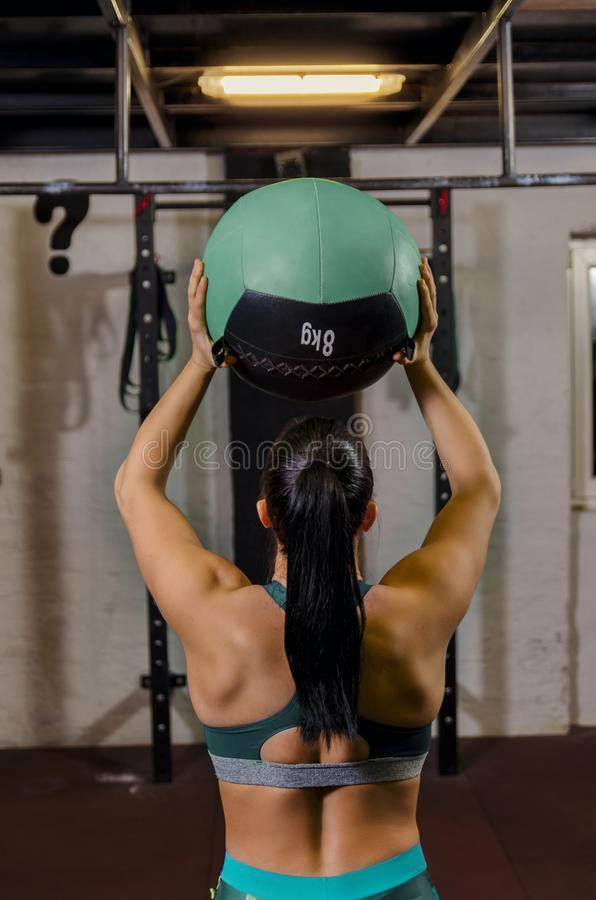Achtermeningsvrouw die zware bal voor oefening houden royalty-vrije stock foto