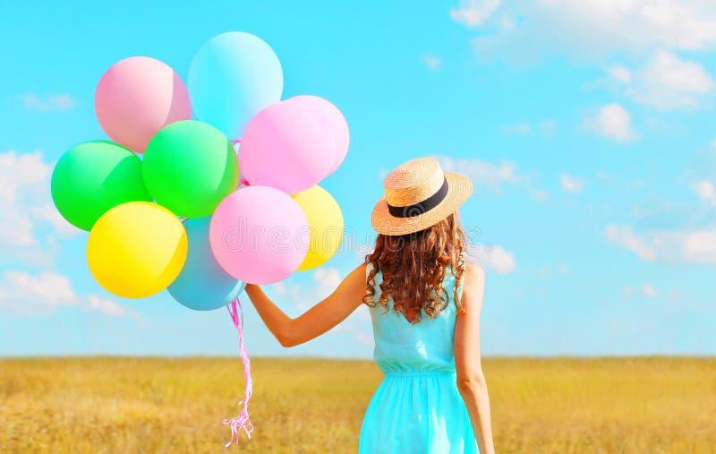 Achtermeningsvrouw met een lucht kleurrijke ballons in een strohoed die van een de zomerdag op een gebied en een blauwe hemel gen royalty-vrije stock foto's