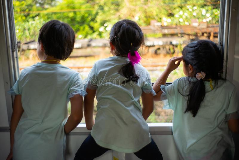 Achterportret van drie zusters die uit het venster van tra kijken stock fotografie