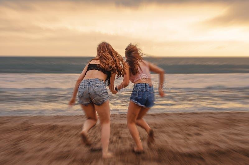Achterportret van twee gelukkige en aantrekkelijke jonge vrouwenmeisjes die handen op het strand houden die aan het overzees onde stock foto