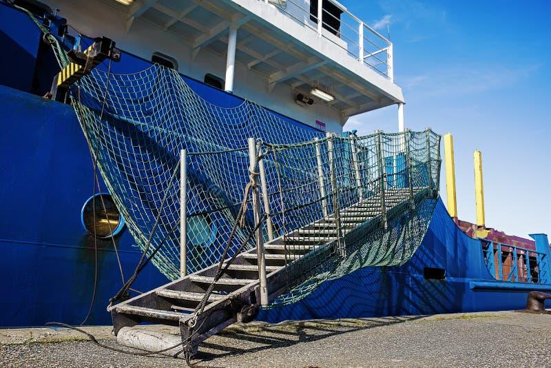 Achtersteven van vrachtschip bij haven Doorgangsarrangment Blauwe schil Witte bovenbouw stock fotografie