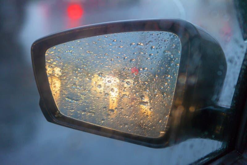 Achteruitkijkspiegel met dalingen van water van de regen en een auto met koplampen Selectieve nadruk, ondiepe dof stock afbeelding