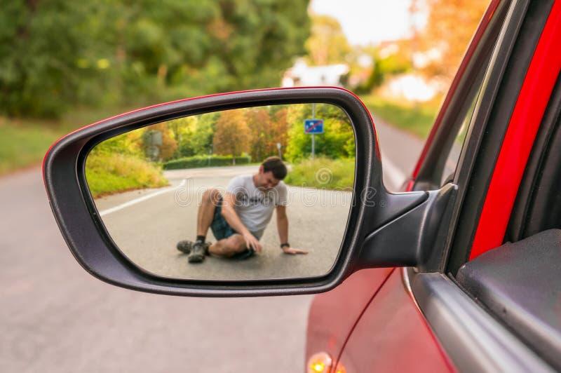 Achteruitkijkspiegel met een mens door een auto wordt geraakt die royalty-vrije stock afbeelding