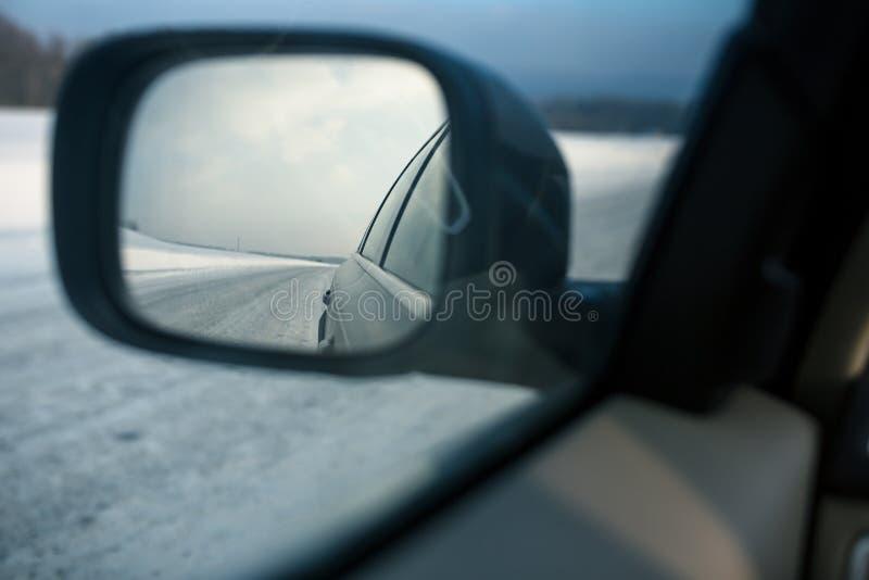 Achteruitkijkspiegel van een moderne auto op een de winterdag stock afbeelding