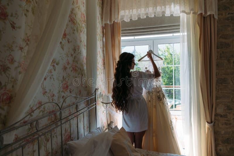 Achtervievbruid in lingerie in de ochtend vóór het huwelijk Wit negligé die van de bruid, voor het huwelijk voorbereidingen treff royalty-vrije stock afbeeldingen