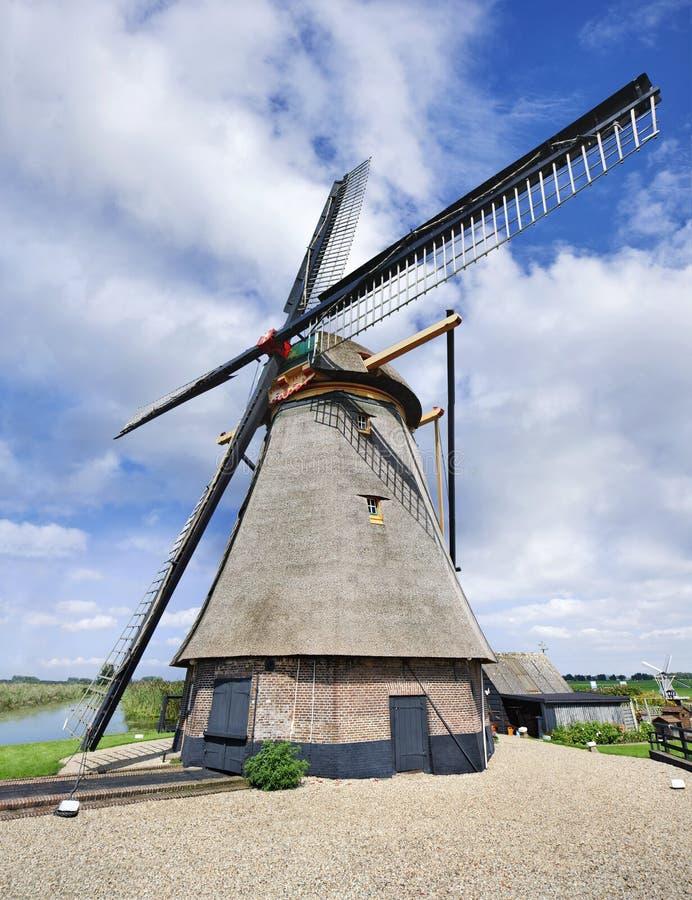 Achthoekige drainagewindmolen met met stro bedekt dakwerk, blauwe hemel en wolken, Nederland stock afbeeldingen