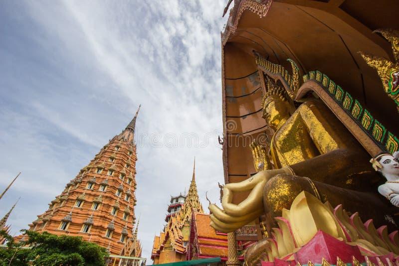 Achthoekige pagode en het grote gouden standbeeld van Boedha bij het Holtempel van Wat Tham SuaTiger, het District van Tha Muang, stock afbeeldingen