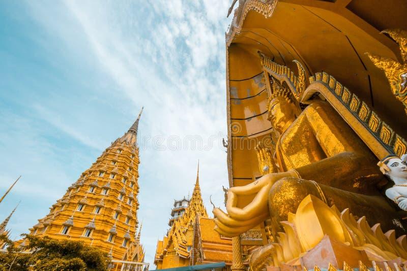 Achthoekige pagode en het grote gouden standbeeld van Boedha bij het Holtempel van Wat Tham SuaTiger, het District van Tha Muang, royalty-vrije stock afbeelding