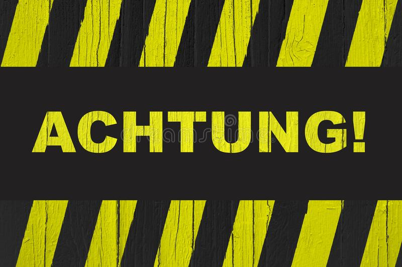 Achtung! in German, Attention! word written on warning sign. With yellow and black stripes painted over cracked wood royalty free stock photography