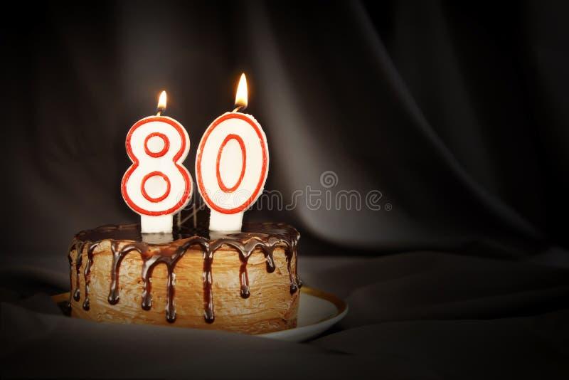 Achtzig Jahre Jahrestag Geburtstagsschokoladenkuchen mit weißen brennenden Kerzen in Form von Nr. achtzig stockbild